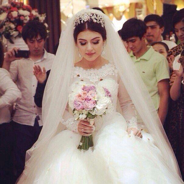 Невеста в белом платье стоя в углу
